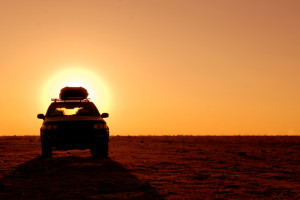 Offroad 4x4 vehicle in the desert at sunrise
